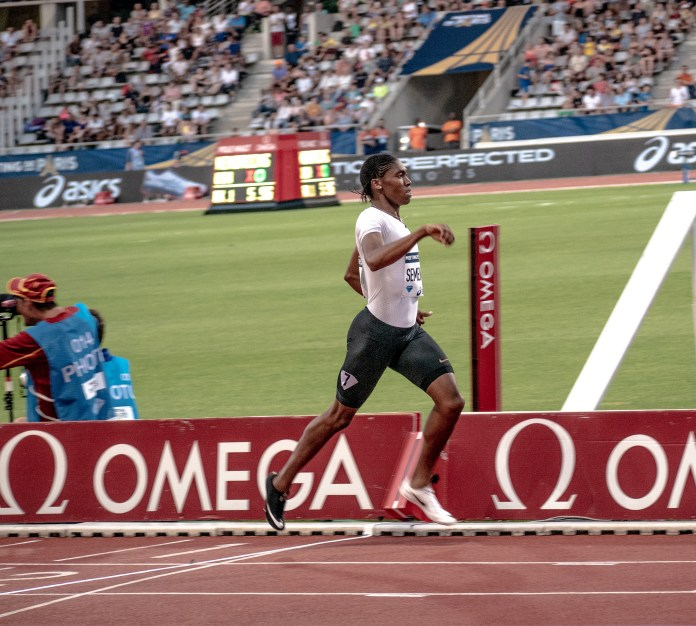 Runner Caster Semenya running across a finish line on a track in a stadium