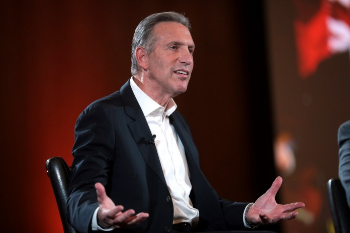 Photograph of former Starbucks CEO sitting on a stage gesturing with his hands spread