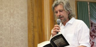 "Photograph of author Karl Ove Knausgard standing, holding a microphone, and reading from a book where the title ""My Struggle"" is visible"