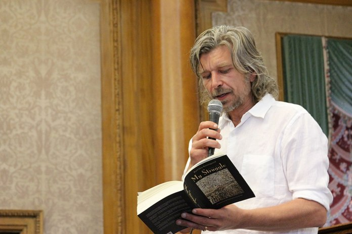 Photograph of author Karl Ove Knausgard standing, holding a microphone, and reading from a book where the title