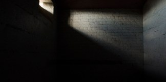 photograph of dark empty cell with small slit of sunshine