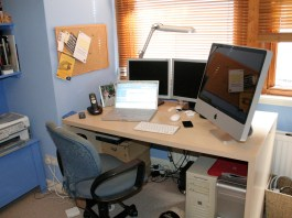 A wooden desk holds up the equipment for an at home office