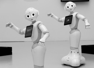 Black and white photograph of two robots with computer displays