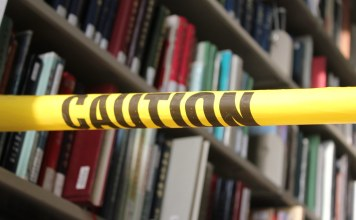 photograph of caution tape around library book shelves