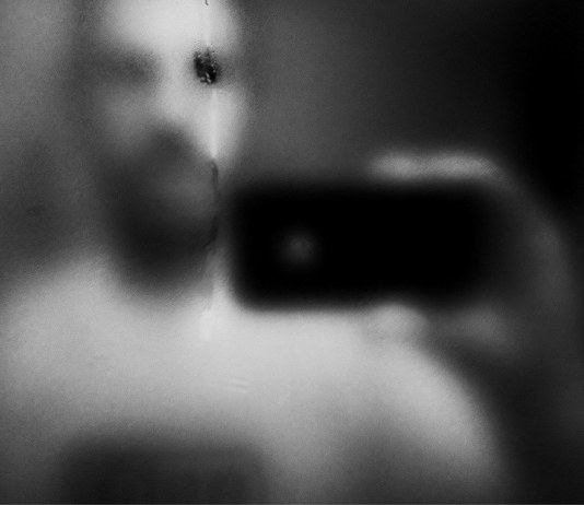 photograph of a man's reflected image on mirror taken by iphone