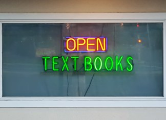 "photograph of neon ""Open"" and ""Textbooks"" signs in window"