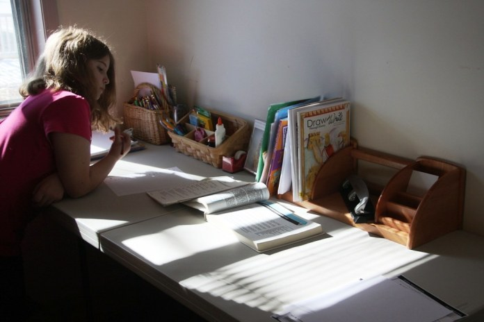 photograph of young girl doing school work in room
