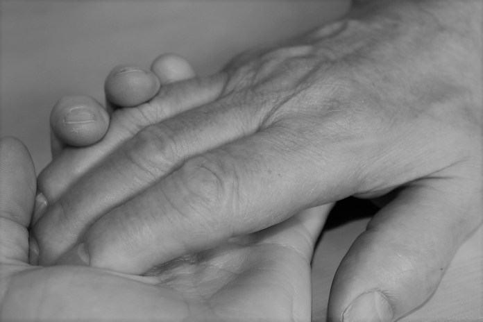 photograph of one hand in another