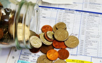 photograph of coin jar spilling out on top of medical bills