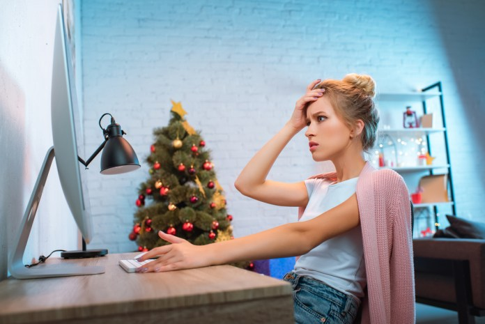 photograph of woman at computer, Christmas tree in background