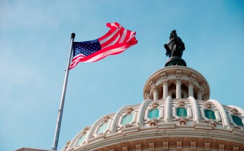 photograph of Capitol building with U.S. flag flying below the Statue of Freedom