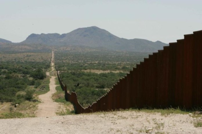 photograph of border wall stretching into the distance