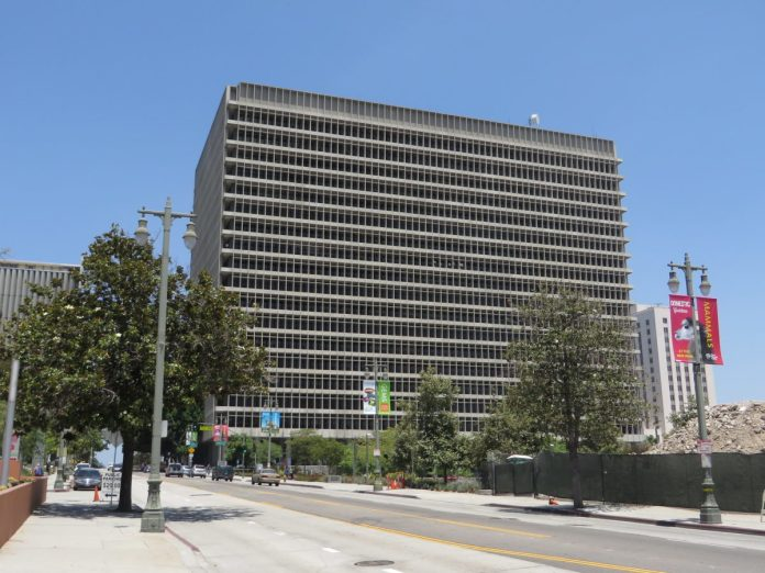 View from street of a large concrete building with thousands of windows. The building is the Los Angeles County Criminal Courts building.