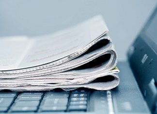 photograph of newspapers folded on top of laptop keyboard