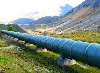 photograph of pipeline through open land with mountains