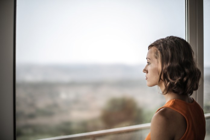 photograph of woman staring off out window