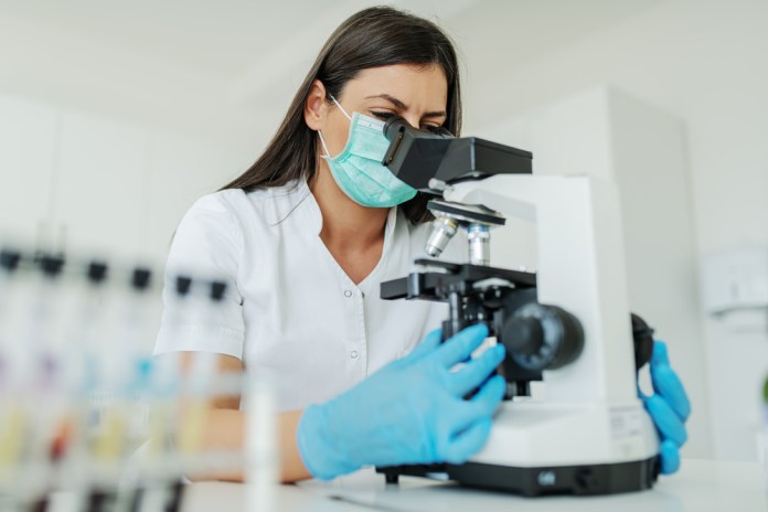 photograph of scientist with mask and gloves looking through microscope