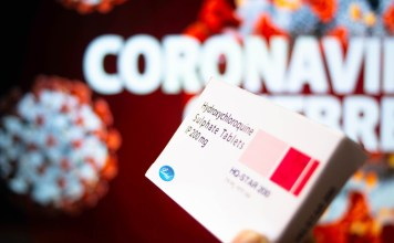 A box of hydroxychloroquine sulphate tablets held by a hand with coronavirus written in background