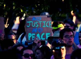 """photograph of """"No Justice No Peace"""" sign at protest"""