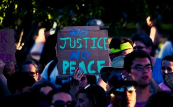 "photograph of ""No Justice No Peace"" sign at protest"