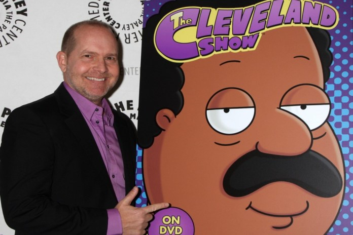 photograph of Mike Henry beside poster of Cleveland character he voices