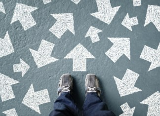 photograph of feet standing before numerous direction arrows painted on ground