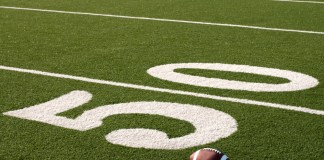 photograph of footbal next to the 50 yard line