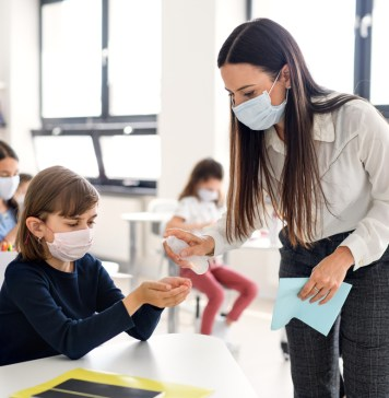 photograph of school children with face masks having hands disinfected by teacher