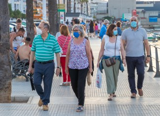 photograph of groups of people walking on busy street wearing protective masks
