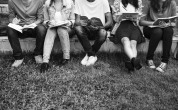 black-and-white photograph of group of students studying outside