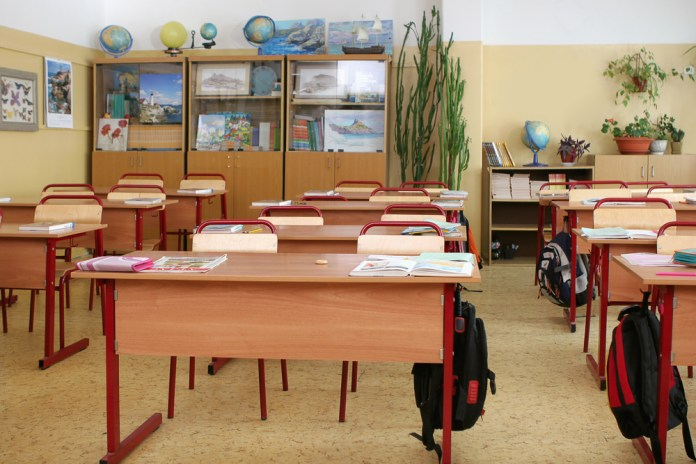 photograph of empty elementary school classroom filled with books and bags