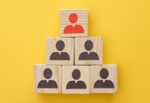 photograph of pyramid of wooden cubes indicating people on yellow background
