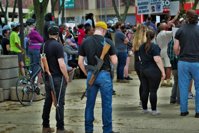 photograph of protesters carrying automatic rifles