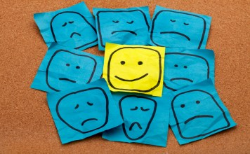 photograph of happy smiley face on yellow sticky note surrounded by sad unhappy blue faces