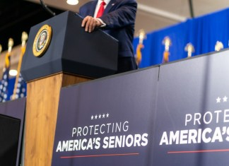 """photograph of """"protecting america's seniors"""" sign next to podium with presidential seal"""