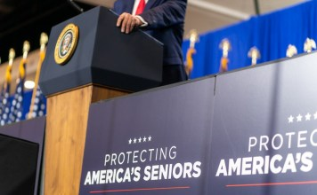 "photograph of ""protecting america's seniors"" sign next to podium with presidential seal"