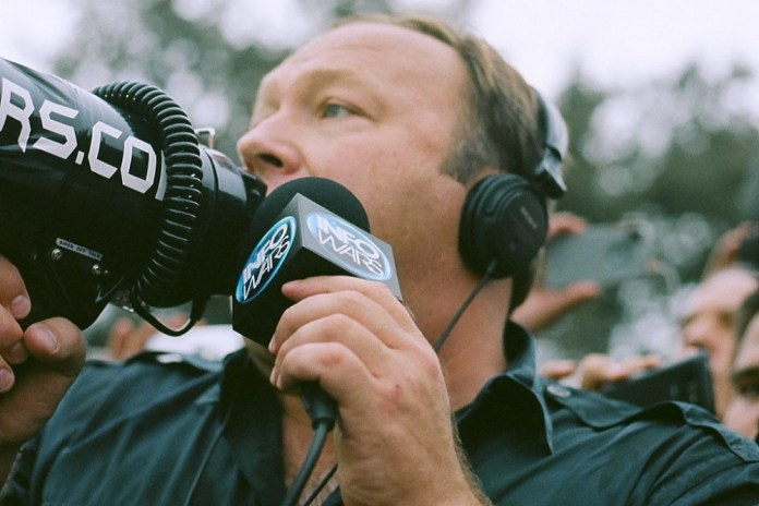 photograph of Alex Jones with megaphone reporting for InfoWars