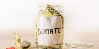 photograph of donation jar stuffed with large bills