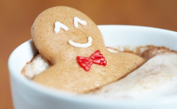 photograph of smiling gingerbread man relaxing in a cup of hot coacoa