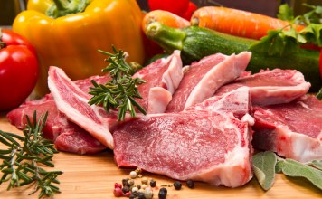 photograph of raw lamb cutlet surrounded by vegetables