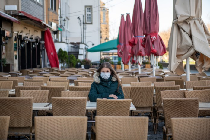 photograph of woman with face mask sitting in large, empty street dining area