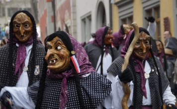 photograph of a crowd marching the streets dressed as witches and wearing grotesque masks