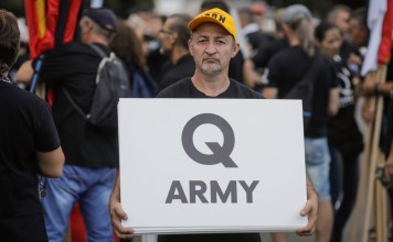 """photograph of 'Q Army"""" sign displayed at political rally"""