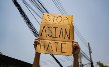 "photograph of ""Stop Asian Hate' sign being held"