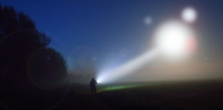 photograph of silhouetted figure shining flashlight at light source in the night sky