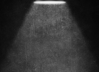 black and white photograph of lamp light in darkness