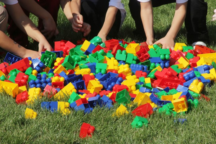 photograph of children playing with LEGOs in the grass