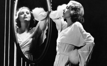 black-and-white photograph of glamorous woman looking in mirror
