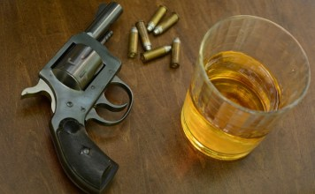 photograph of gun with bullets and glass of alcohol on table