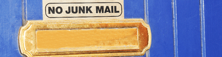 A gold letter box on a blue door with a sign that reads no junk mail.
